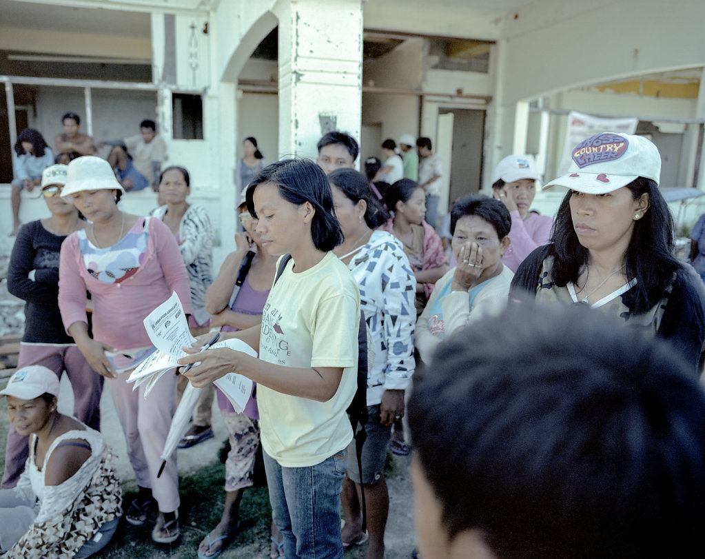 At an old abandoned house on the beach in Tacloban, materials to rebuild huts, are distributed.  A lady from the government, keeps abreast, with what families who have received.