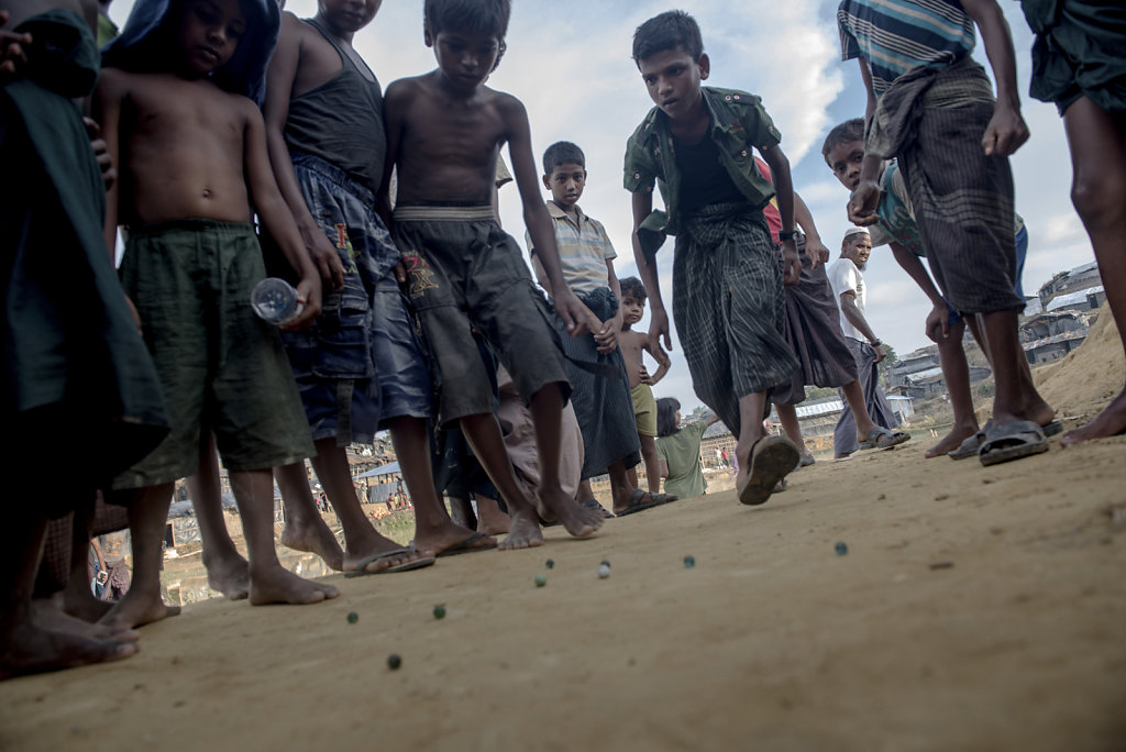 On a plateau, a group of boys has got together in playing with marbles. For a moment, the horrors they have experienced in Myanmar are forgotten.